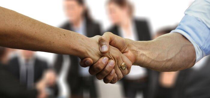 Kvinde og mand giver håndslag